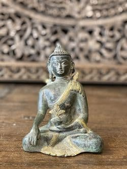 Bronze and golden medicine buddha in enlightenment pose